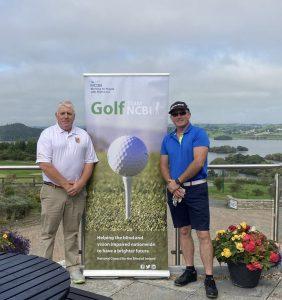 2 men standing beside NCBI Golf sign